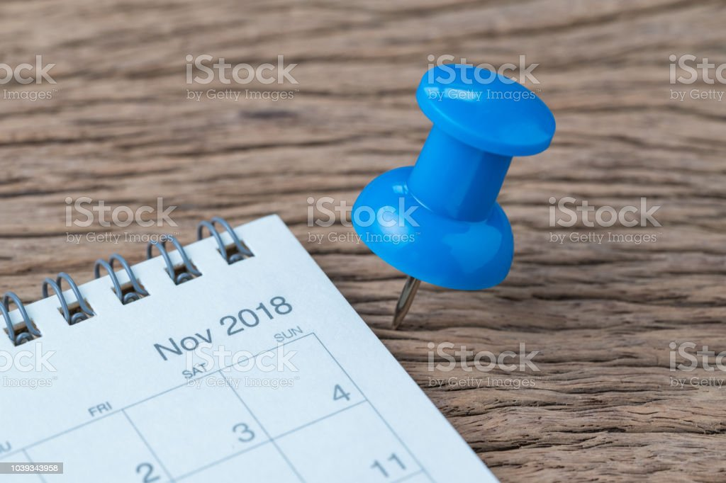 November 2018 calendar appointment, deadline, holiday or date planning concept, big blue pushpin or thumbtack pin on wooden table next to Nov white clean calendar. stock photo