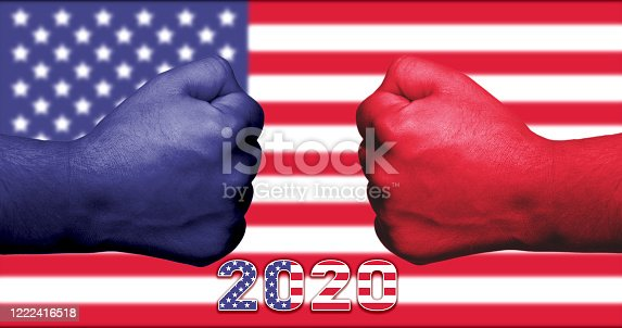1157022917 istock photo November 2020 American presidential elections concept with blue and red fists facing each other and the USA flag in the background. 1222416518