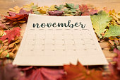 November calendar on paper sheet surrounded by multiple autumn leaves of vivid colors