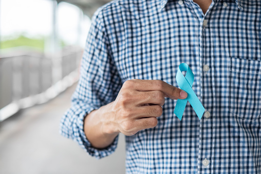 1168142443 istock photo November Prostate Cancer Awareness month, Man in blue shirt with hand holding Blue Ribbon for supporting people living and illness. Healthcare, International men, Father and World cancer day concept 1168853390