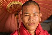 istock Novice Buddhist monk holding umbrella, Myanmar 1216592031