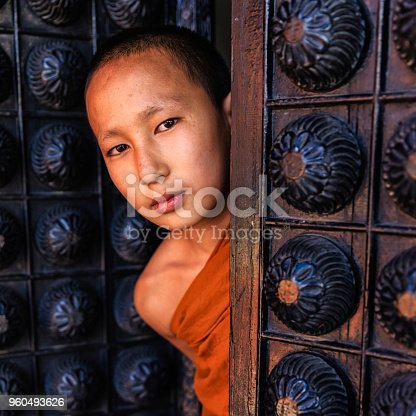Novice Buddhist monk looking out of the doors in the monastery in Bhaktapur, Nepal