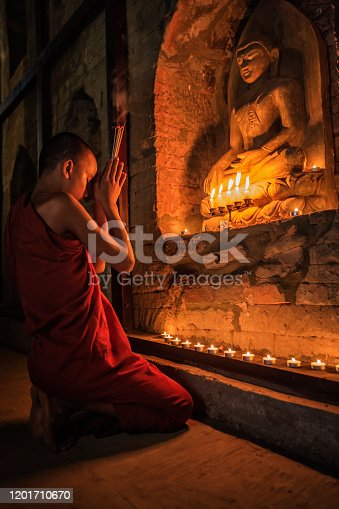 Two young buddhist monks praying inside an ancient temple, Bagan, Myanamar