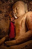 istock Novice buddhist monks contemplating inside temple, Myanmar 1220497084