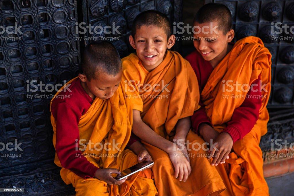 Novice Buddhist monks playing on mobile phone, Bhaktapur stock photo