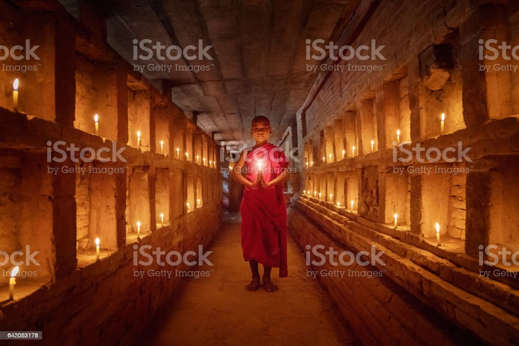 Novice Monk praying inside temple full burning candles Bagan Myanmar stock photo