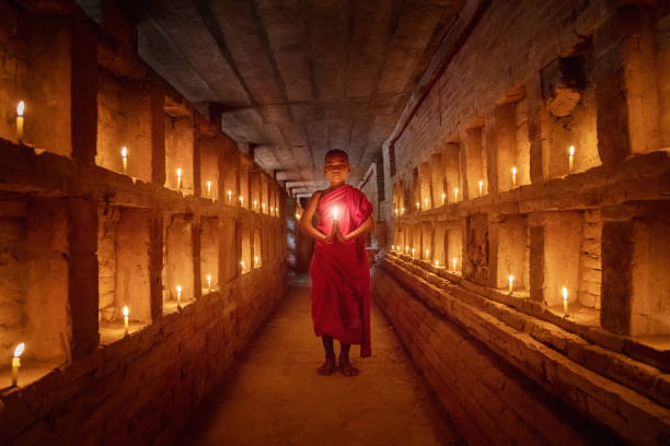novice monk praying inside temple full burning candles bagan myanmar - crypt stock pictures, royalty-free photos & images