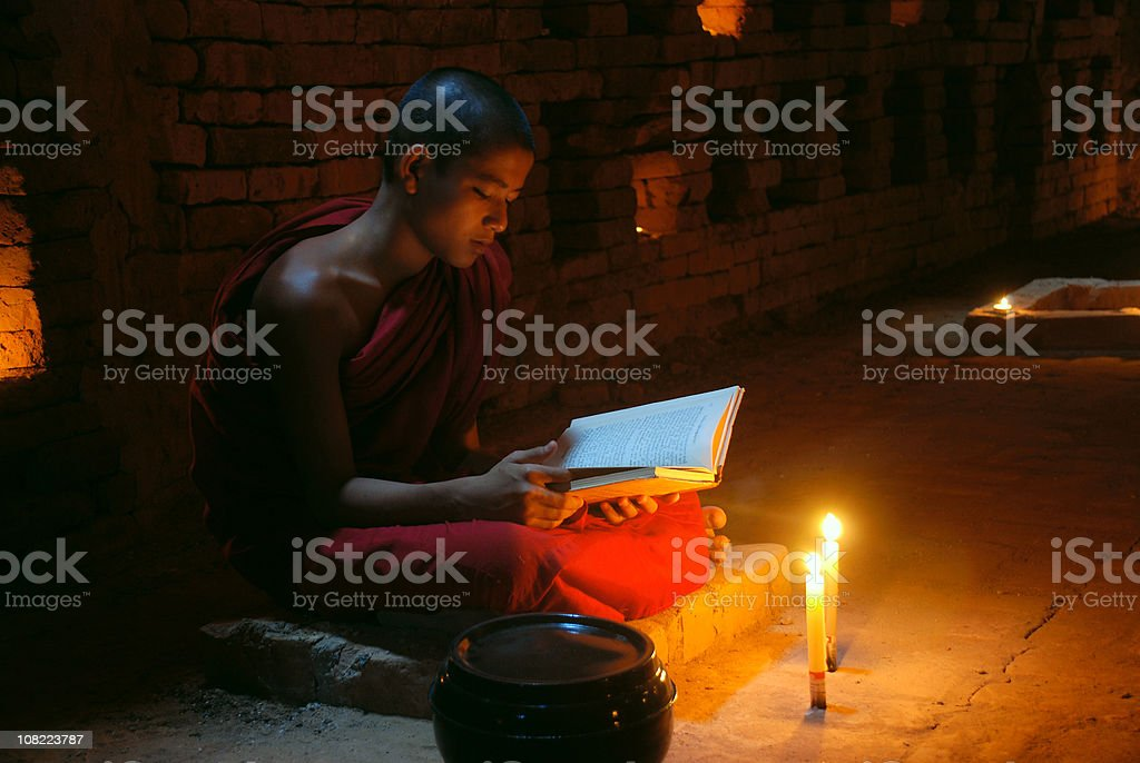 Novice monk reading book in temple royalty-free stock photo