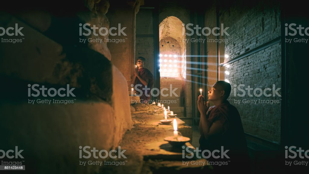 Novices praying with candles stock photo