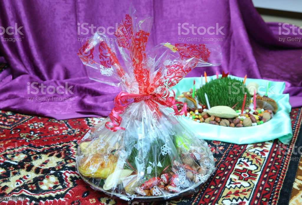 Novruz concept plate of traditional Azerbaijan pastries packlava and shekerbura in copper vintage tray with wheat grass semeni on white wooden table background, stock photo