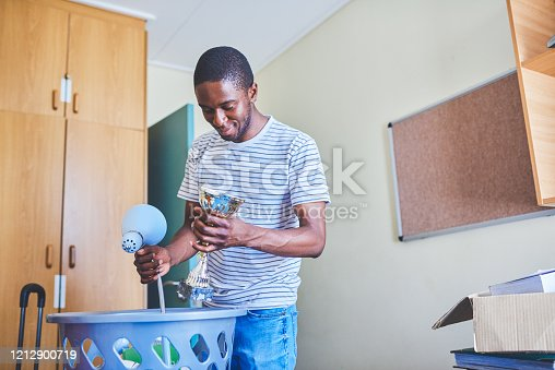 Cropped shot of a cheerful young man unpacking his stuff after arriving at his new home inside during the day