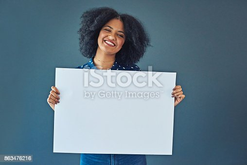 Studio shot of a young woman holding up a blank placard against a gray background