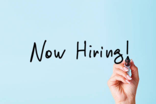 Now hiring poster Now hiring a poster for finding personnel in the company. Female hand with a black marker draws words on the blackboard. help wanted sign stock pictures, royalty-free photos & images