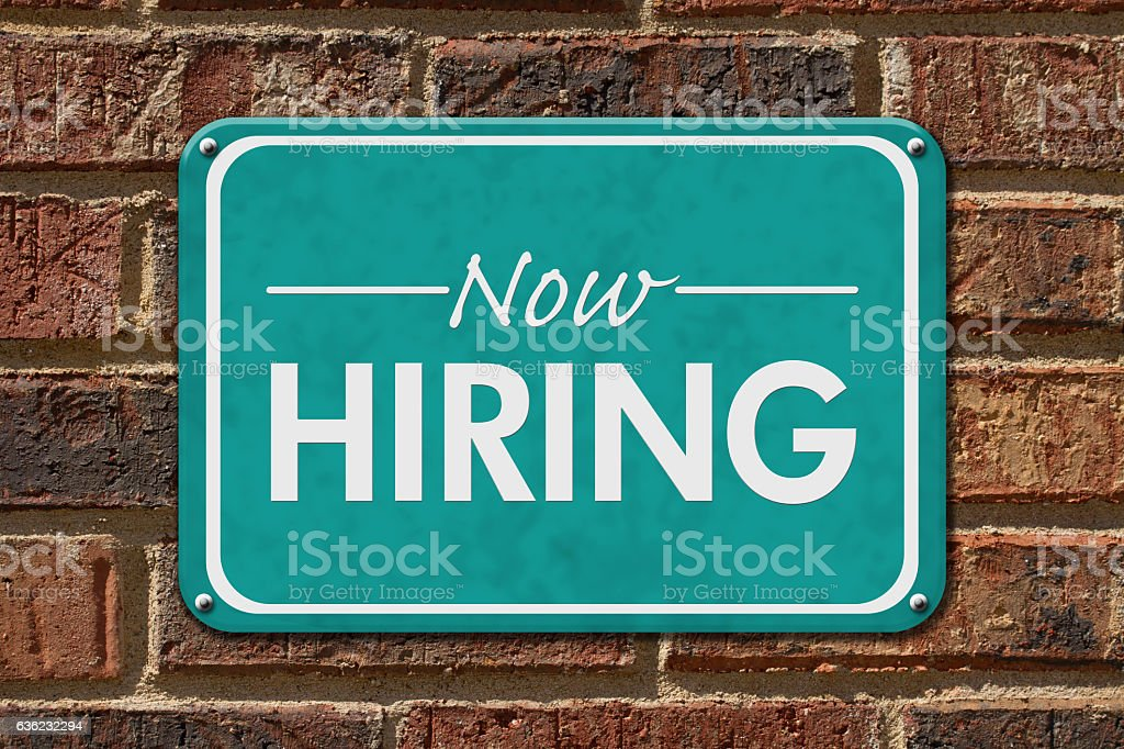 Now Hiring Sign on a brick building stock photo