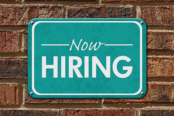 Now Hiring Sign on a brick building Now Hiring Sign, A teal sign with text Now Hiring on a brick building help wanted sign stock pictures, royalty-free photos & images
