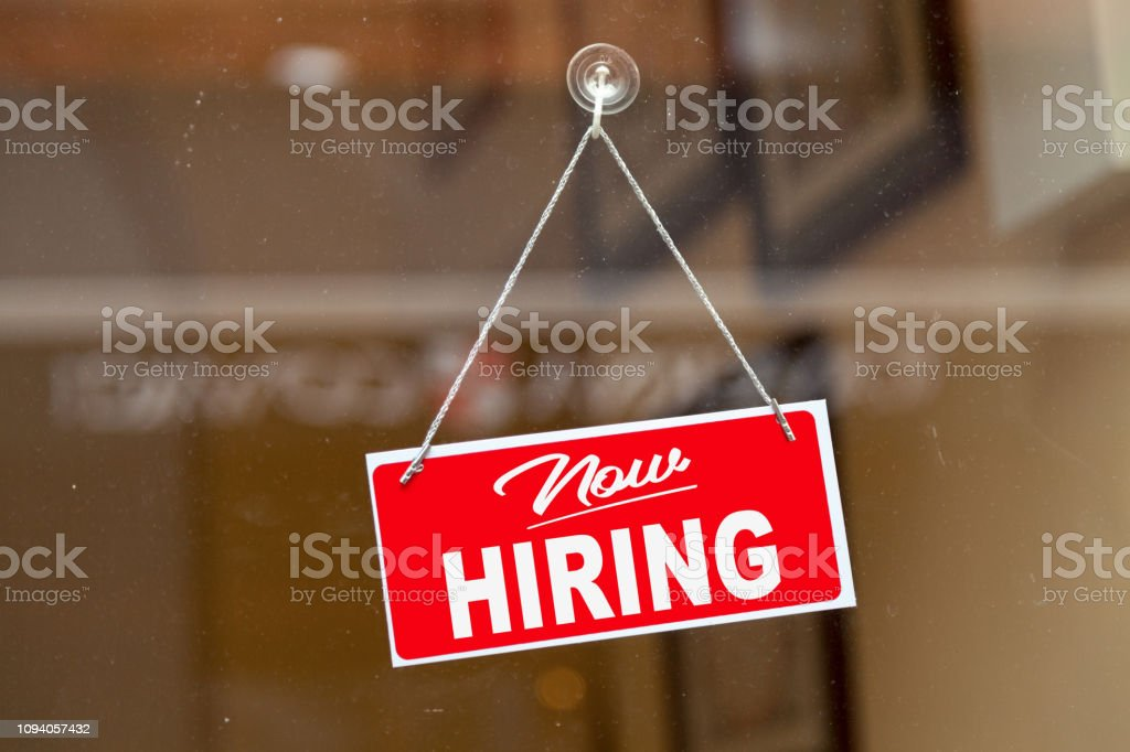 """Now hiring sign Red sign hanging at the glass door of a shop saying: """"Now hiring"""". Business Stock Photo"""