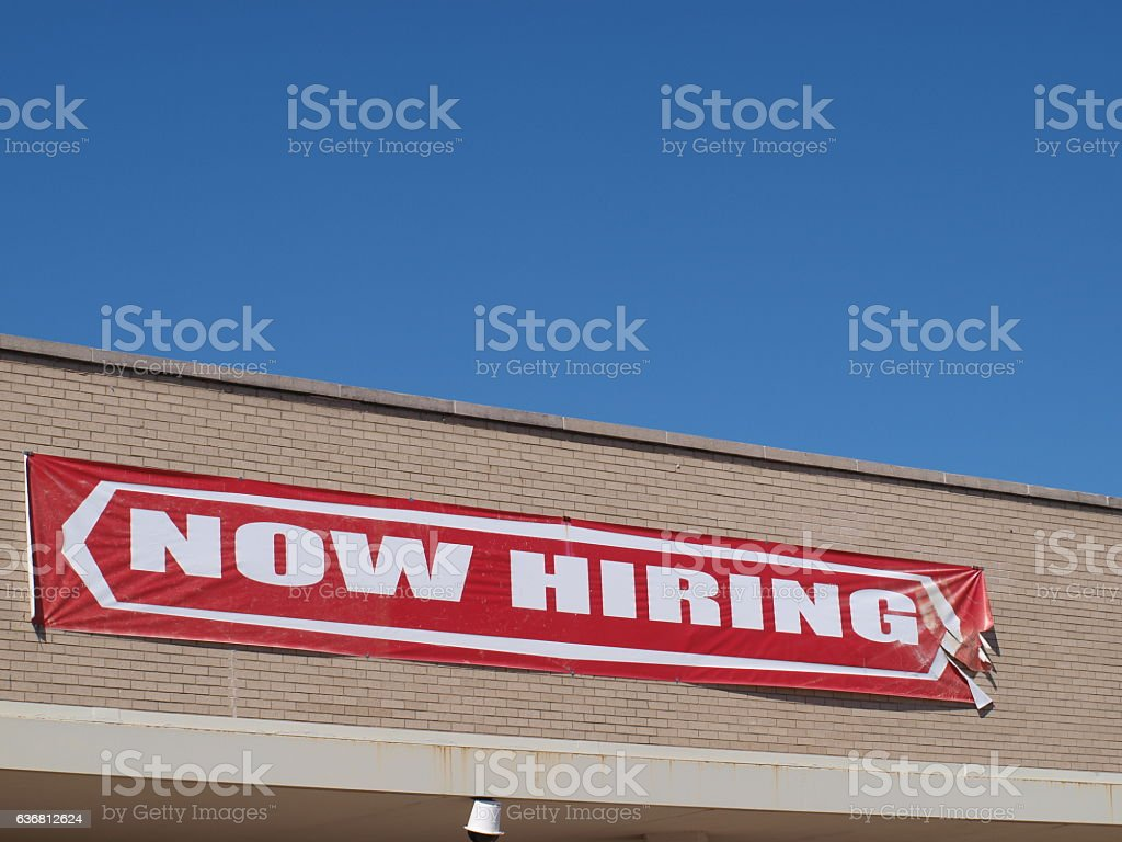 Now Hiring Sign A now hiring sign hangs on the side of a building in Dallas. Job signs are in demand for construction workers especially.  Business Stock Photo