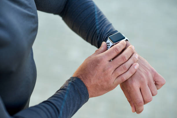 Now is the time! Closeup shot of an unrecognizable man checking his smartwatch while exercising outdoors fitness tracker stock pictures, royalty-free photos & images