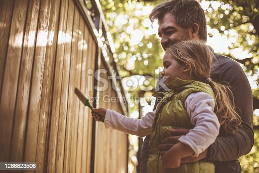Copyspace of father and daughter painting together a wooden door of their backyard during stay at home order.
