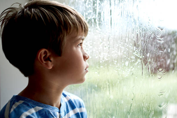 Now my friends can't come over Shot of a little boy sitting by the window while watching the rain boy looking out window stock pictures, royalty-free photos & images