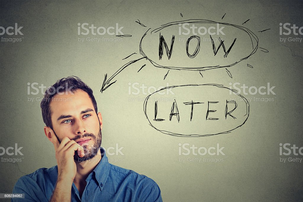 Now or later. Man thinking looking up stock photo