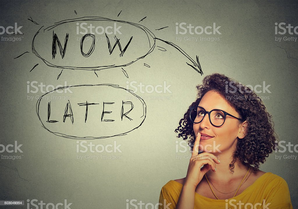 Now or later. Woman thinking looking up. Human face expression stock photo