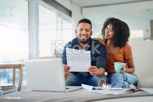 Shot of a happy young couple looking going over their finances at home