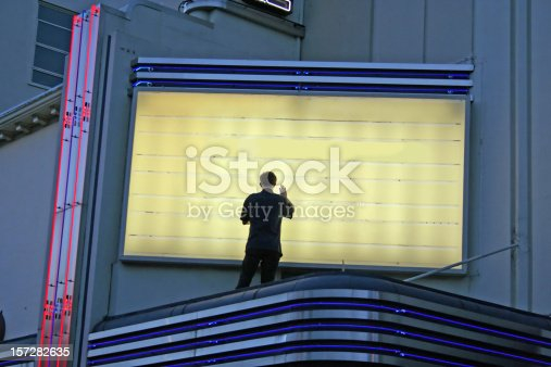 istock Now Showing! Man Changing Sign 157282635