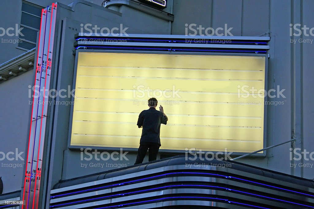 Now Showing! Man Changing Sign stock photo