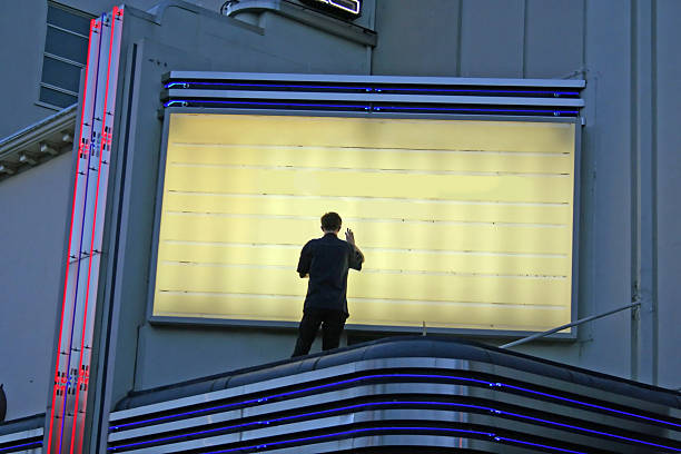 Now Showing! Man Changing Sign Changing Movie Currently Playing - Great for any communication of a change with room to put your text theater marquee commercial sign stock pictures, royalty-free photos & images