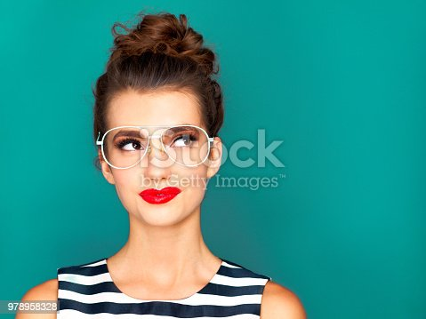 Studio shot of a beautiful young woman posing against a turquoise background