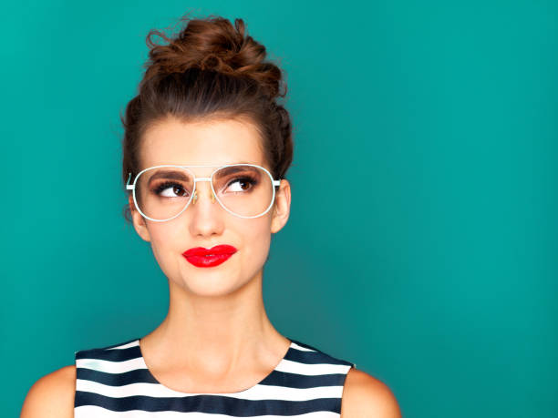 Now that's an idea Studio shot of a beautiful young woman posing against a turquoise background eyewear stock pictures, royalty-free photos & images