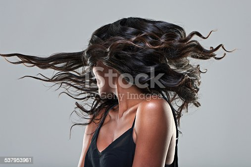 Studio shot of a young woman with beautiful hair isolated on gray