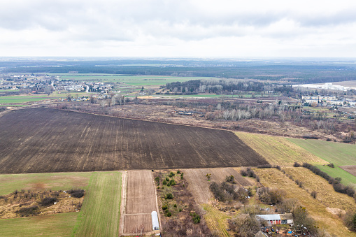 istock Nowy Dwor, Poland above view from window near airport with rural winter brown plowed landscape countryside town village near Warsaw and farm fields greenhouse 1217468806
