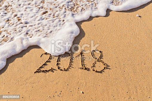 istock nscription Number 2018 handwritten on seashore sand 899389858