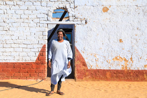 nubian man wearing traditional clothing standing in front of the house. - north africa stock photos and pictures