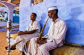 'Two Muslim men smoking sheesha (waterpipe) in Nubian Village near Aswan, Southern Egypt, Africa.'