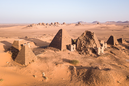 a group of pyramids, partially ruins, at Meroe in Sudan embedded in sand dunes with more pyramids in the background photographed from drone