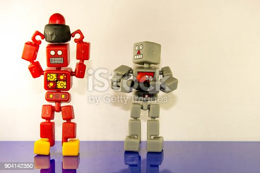Two robots stand holding their 'Nuclear Buttons' comparing size.