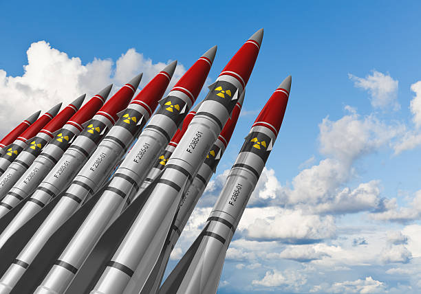 Nuclear missiles against blue sky Row of heavy nuclear missiles against blue sky with clouds. See also: radioactive contamination stock pictures, royalty-free photos & images