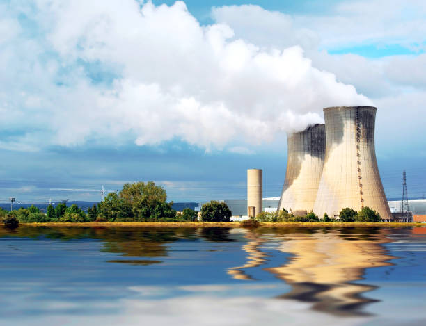 Nuclear plant. Chimneys of the plant emitting steam. The cooling is provided by the river water. nuclear power station stock pictures, royalty-free photos & images