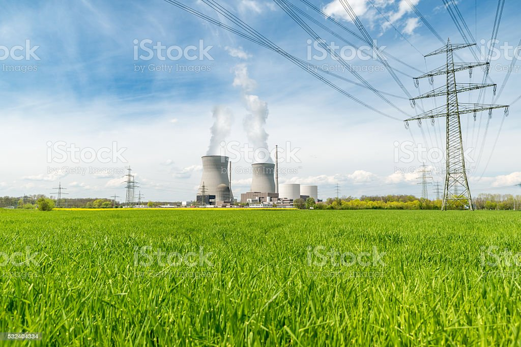 Nuclear power plant with green field and big blue clouds stock photo