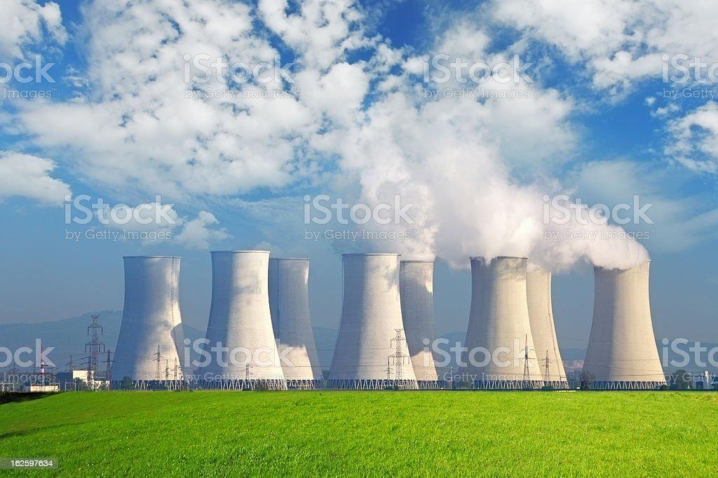 Nuclear power plant with yellow field and big blue clouds stock photo