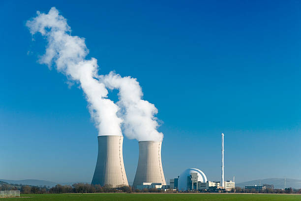 Nuclear power station Grohnde with blue sky Nuclear power station with two steaming cooling towers in blue sky.  nuclear power station stock pictures, royalty-free photos & images