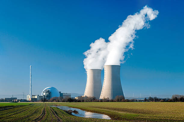Nuclear power station Grohnde with steaming cooling towers Nuclear power station countryside with two steaming cooling towers and blue sky.  nuclear power station stock pictures, royalty-free photos & images