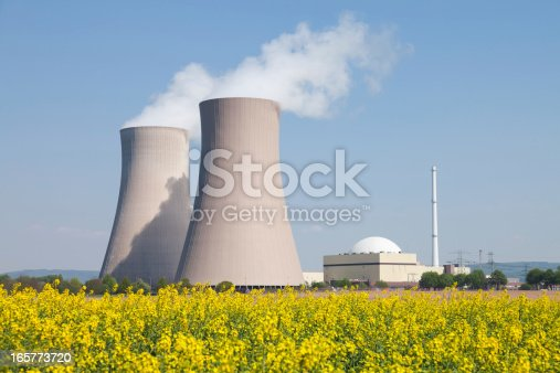 Nuclear power station with steaming cooling towers and blooming canola field. Location: Lower Saxony, Germany.
