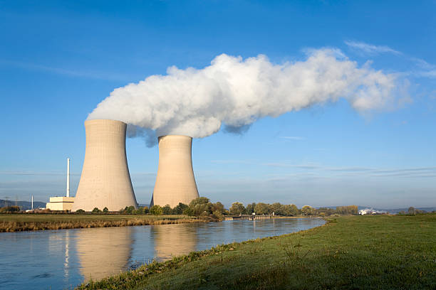 Nuclear power station with two steaming cooling towers riverside (XXXL) Nuclear power station riverside with two steaming cooling towers and blue sky in morning light. Location: Lower Saxony, Germany. nuclear power station stock pictures, royalty-free photos & images