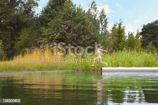 509813720 istock photo Nude child jumping into lake from pier 138300900