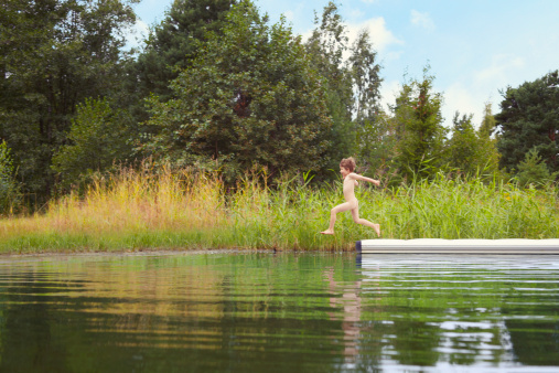 Nude Child Jumping Into Lake From Pier Stock Photo