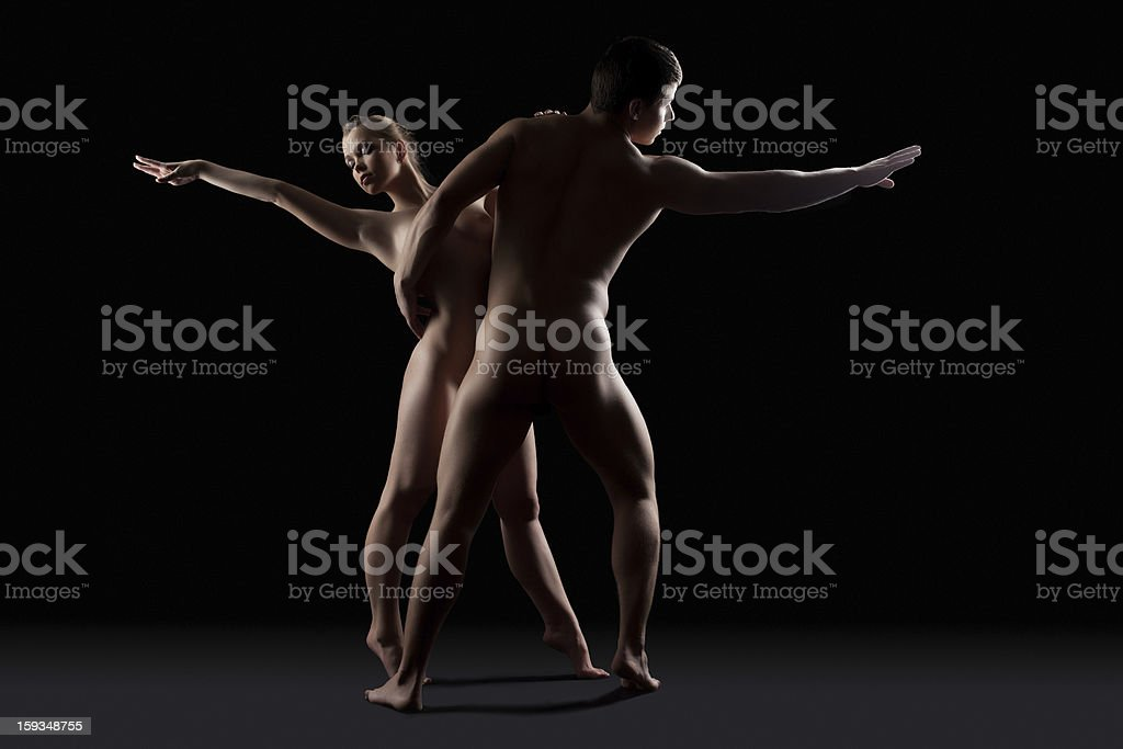 Nude couple of man and woman dance in dark royalty-free stock photo